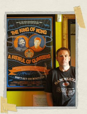 'Philip posing with a movie poster from The King of Kong in Funspot